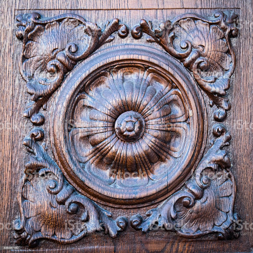 Flower engraved on the wooden portal of an ancient church. stock photo