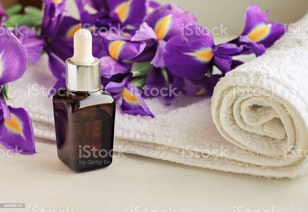 Flower essence dropper bottle,violet Iris, white terry towel wrap stock photo