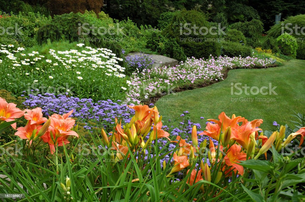 A flower garden with a variety of colored flowers in grass stock photo