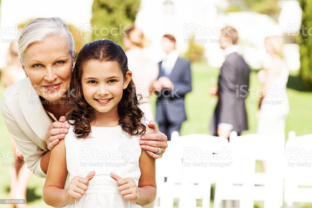 Flower Girl And Grandmother Smiling Together At Outdoor Wedding royalty-free stock photo