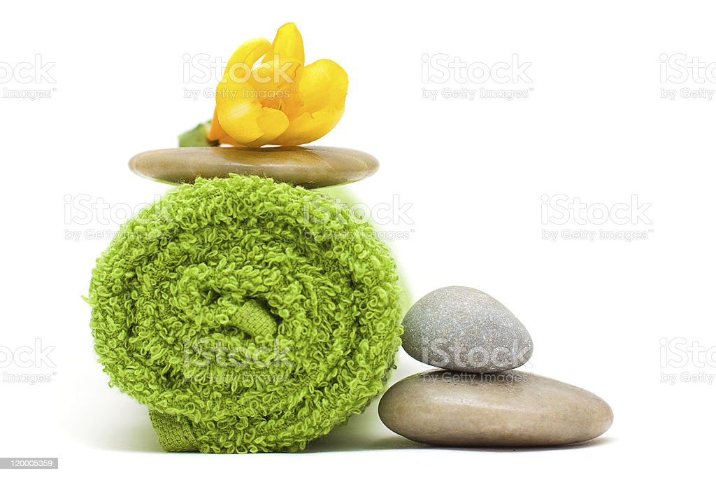Flower, green towel, river stones on white royalty-free stock photo