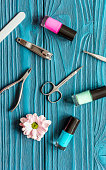 flower, nail polish and manicure set on dark wooden background
