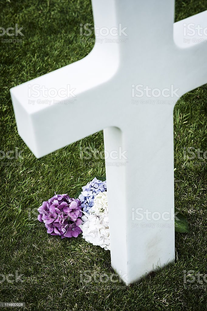 Flower near white cross in a cemetery stock photo