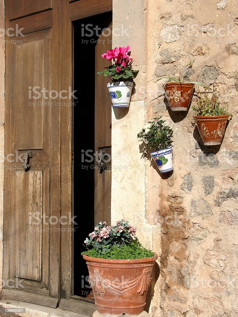 Flower pots at the wall and an open door stock photo