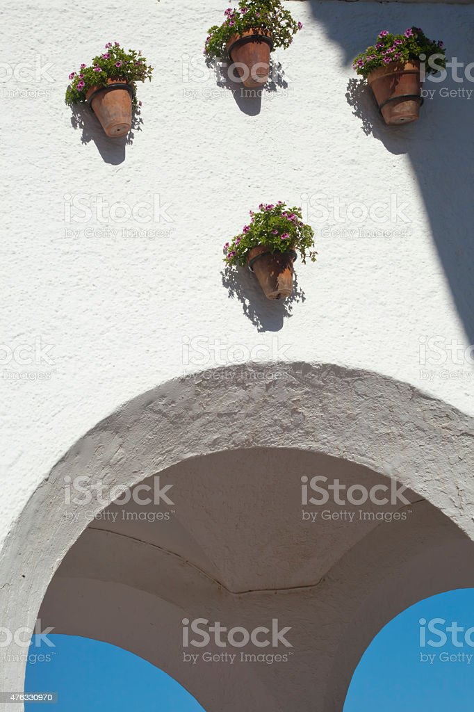 Flower pots hanging above white archs stock photo