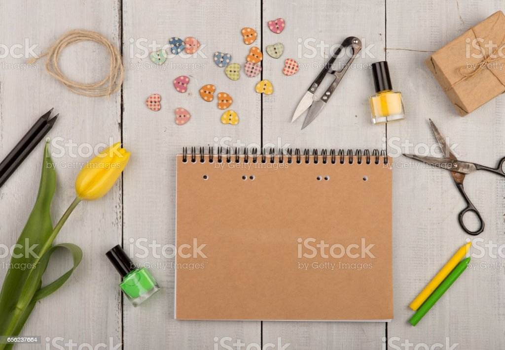 Flower tulip, blank note pad, scissors, nail polish and buttons stock photo
