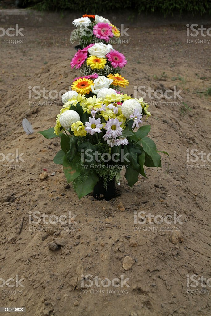 Flower vases on a fresh grave mound stock photo