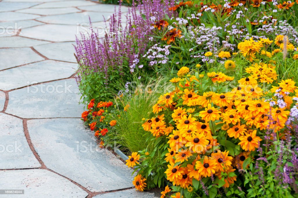 Flowerbed and paving stone slates stock photo