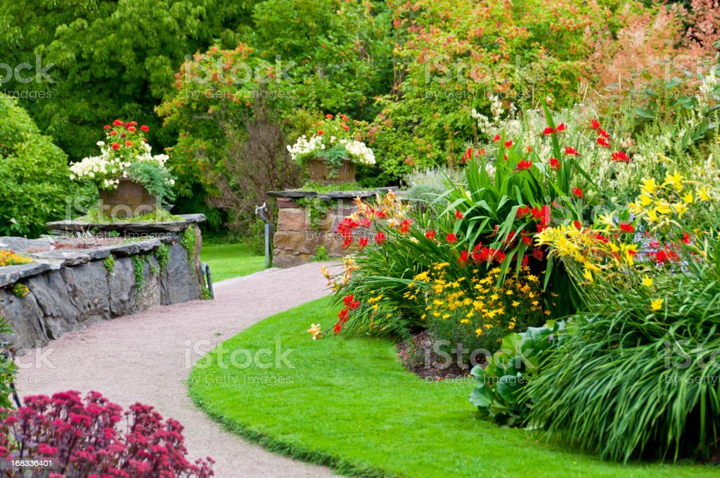 Flowerbeds, flowerpots and stone wall stock photo