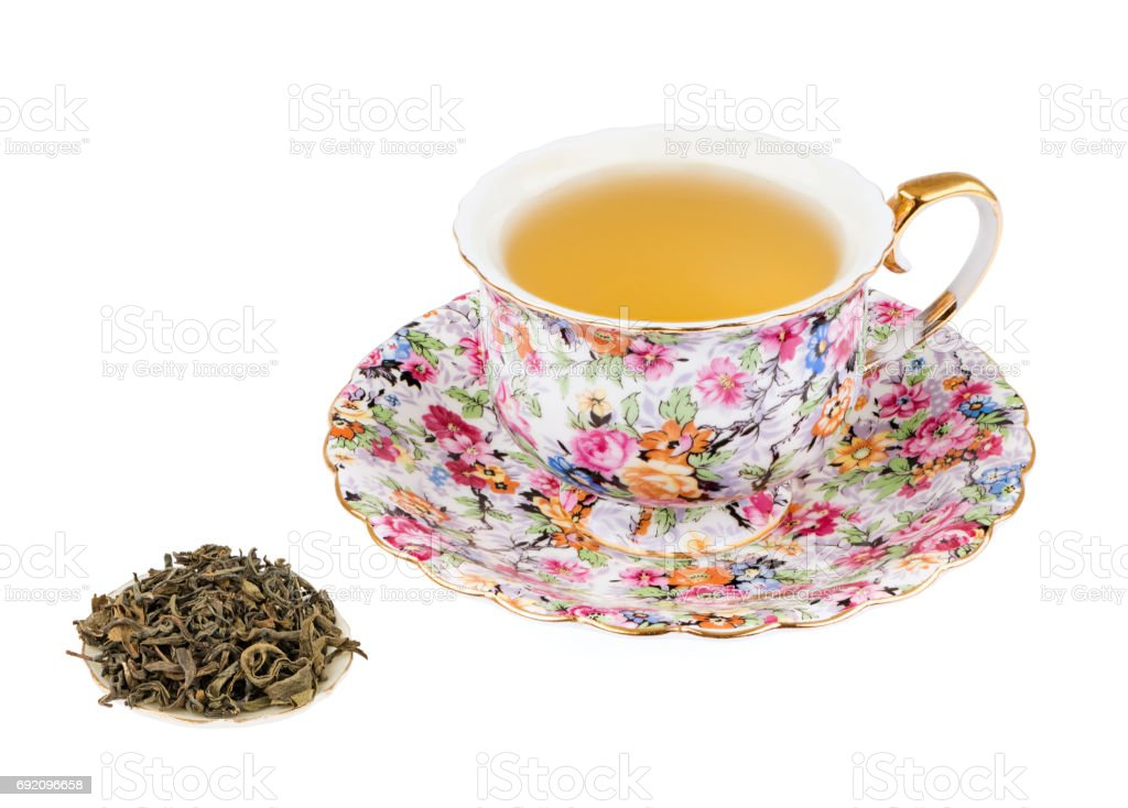 Flowered Tea Cup with Green Tea and Isolated on a White background with Deep Sharp Focus stock photo