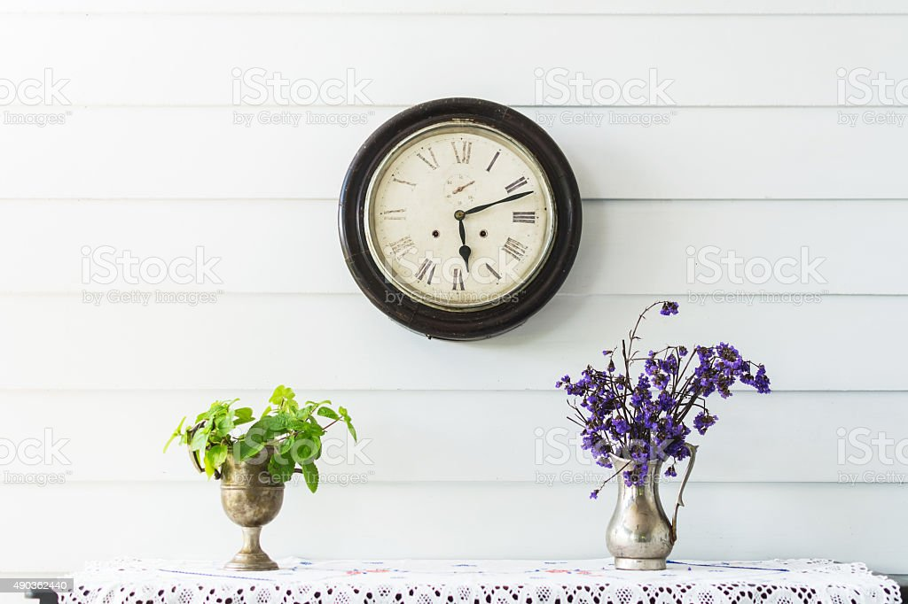 Flowers and a vintage clock on a white wall shelf. stock photo
