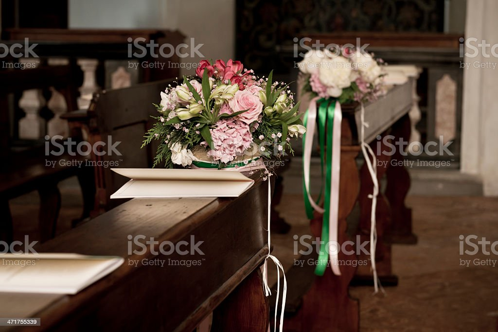 Flowers and booklets on church bench for wedding royalty-free stock photo