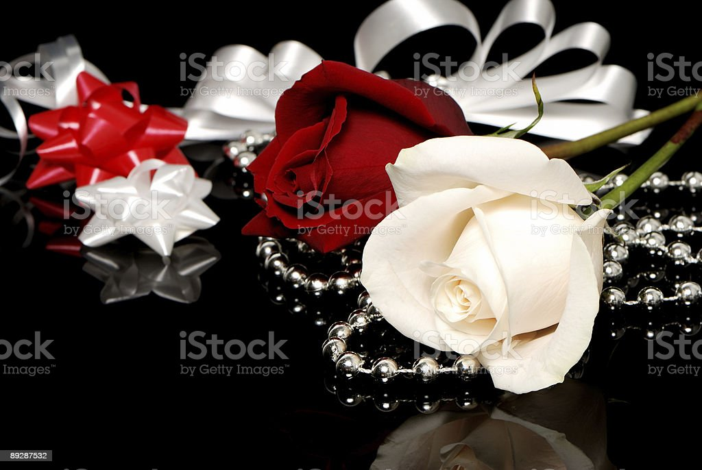 Flowers and Celebratory tapes, bows. Beads on a black background royalty-free stock photo