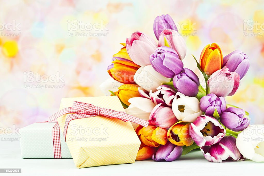 Beautiful bunch of tulips and two wrapped gifts.