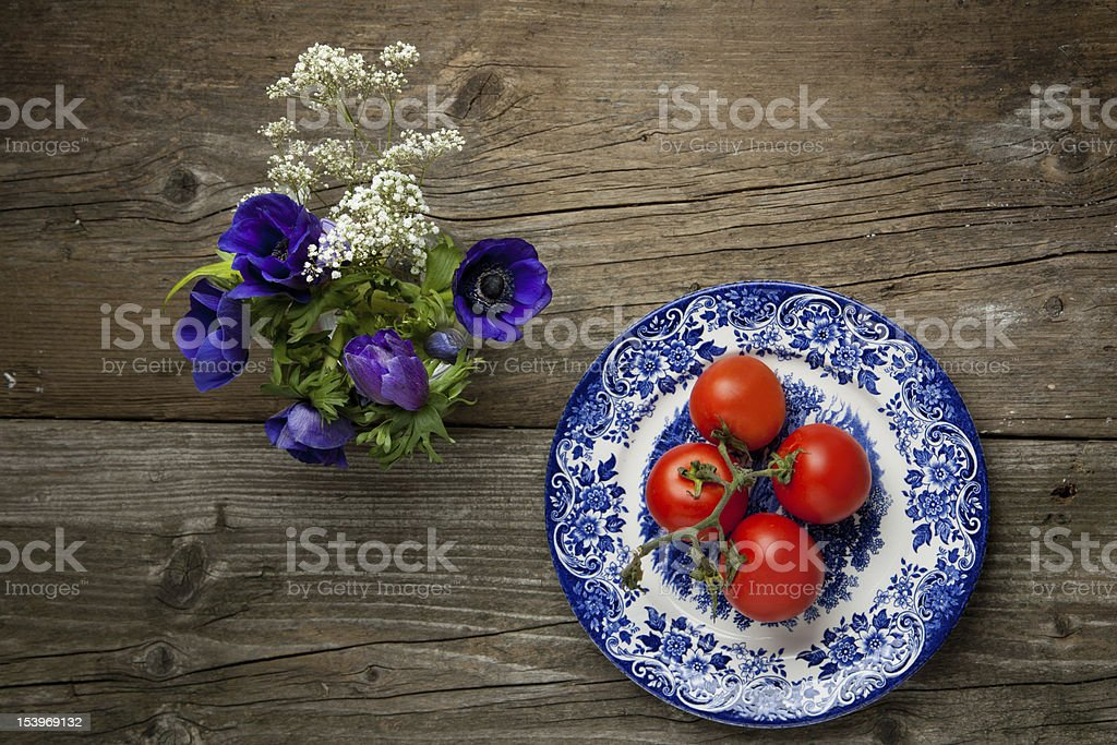 Flowers and plate with fresh tomatos royalty-free stock photo