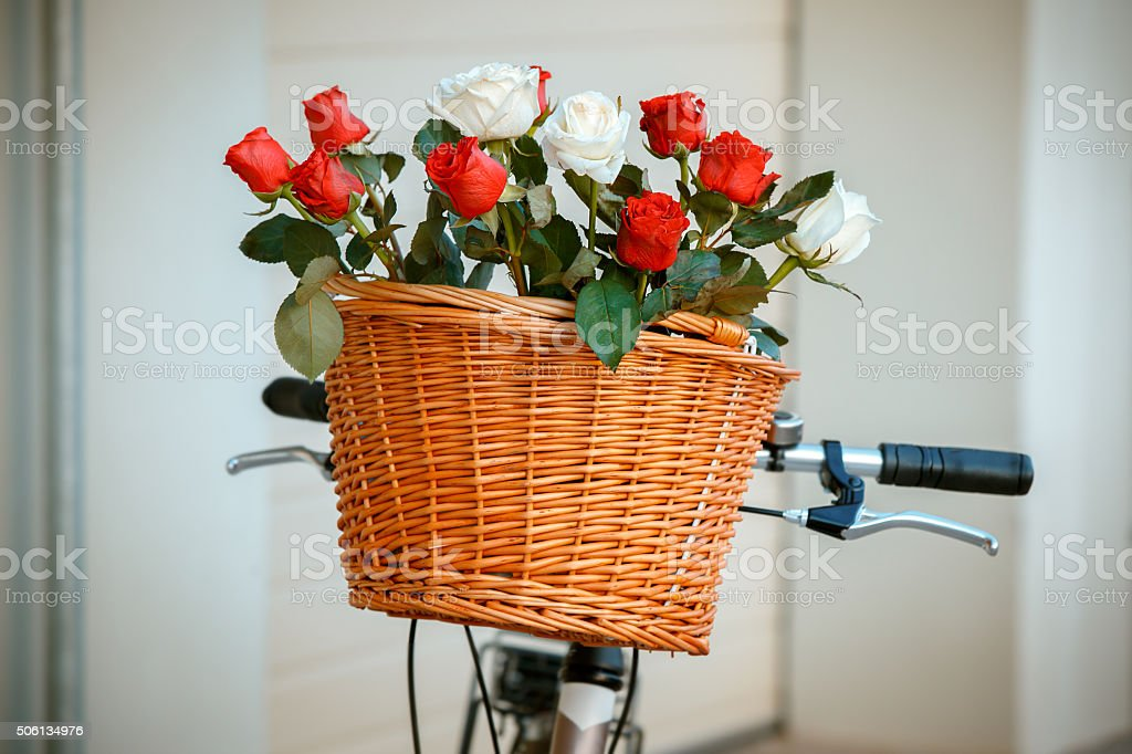 Flowers in basket hanging at bicycle handlebars stock photo