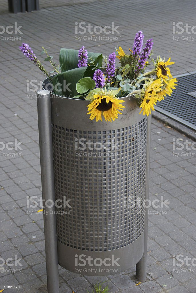 Flowers in rubbish bin stock photo