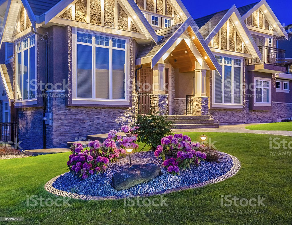 Flowers in the front garden of a well-lit house at dusk  stock photo