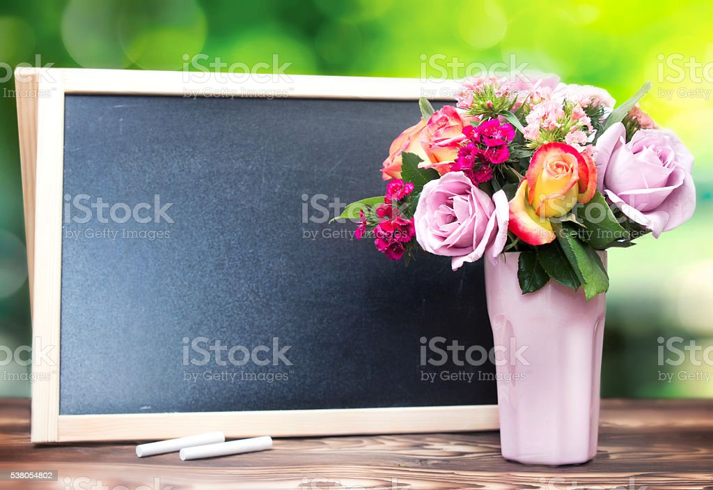 Flowers in vase and chalckboard empty copy space background. stock photo