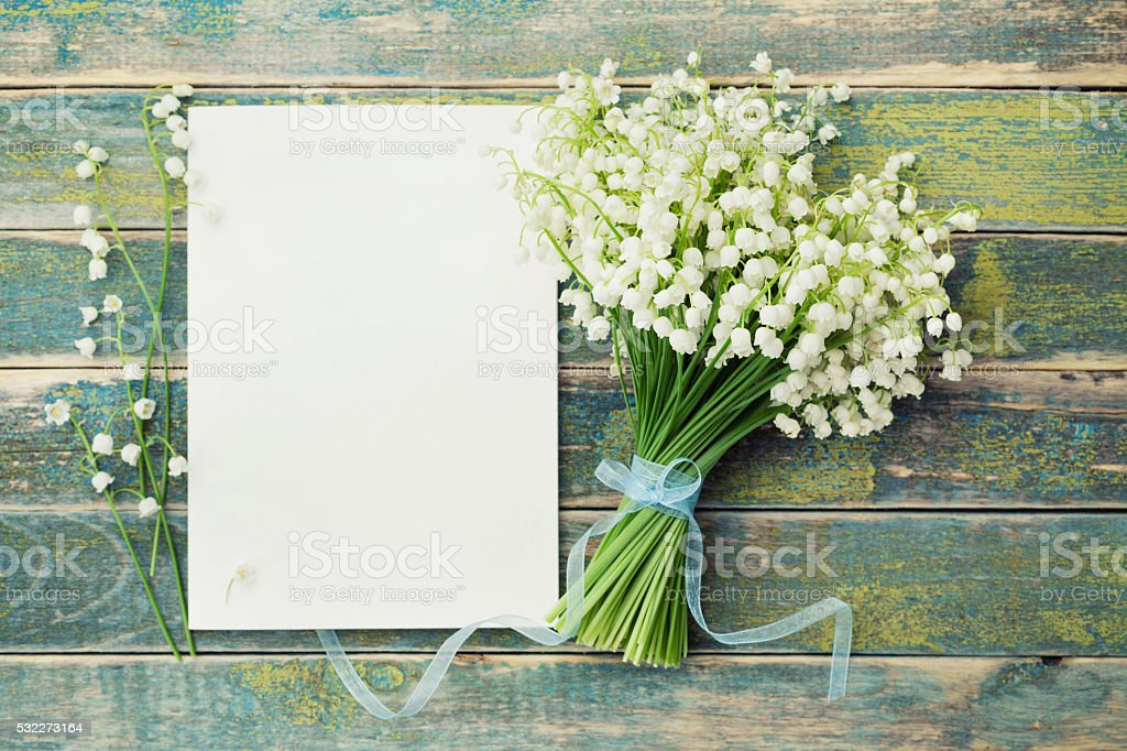 Flowers lily of the valley and empty paper sheet stock photo