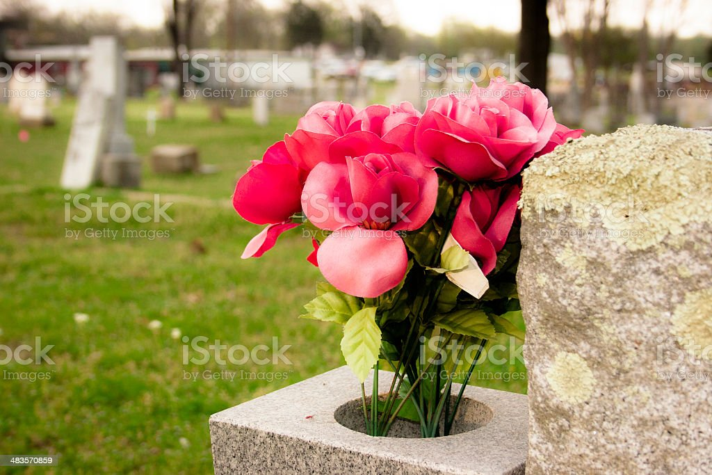 Flowers on grave in cemetary. Tombstones. stock photo