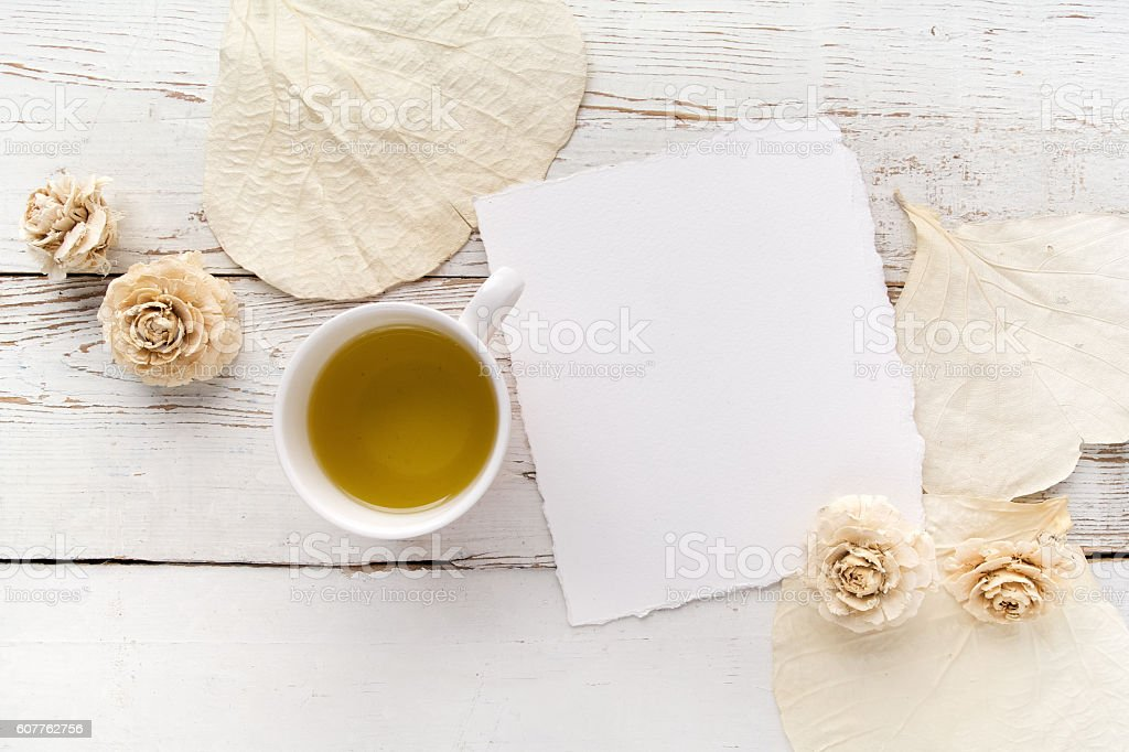 flowers on white wooden table with blank pages and cup stock photo