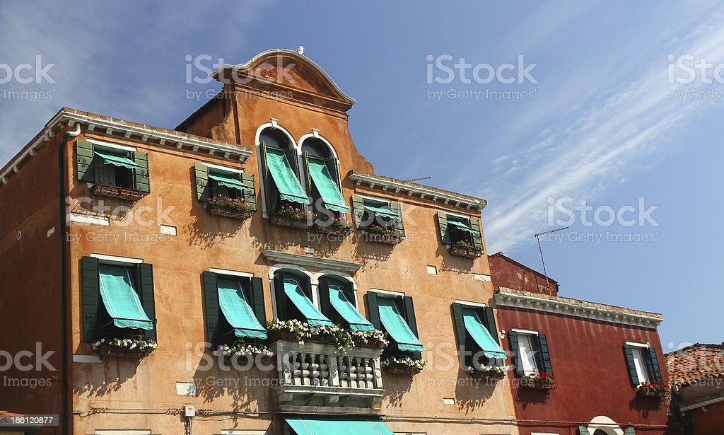flowery balcony in Venetian style with Windows and green awnings royalty-free stock photo