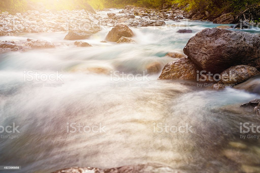 flowing water in a riverbed early in the morning stock photo