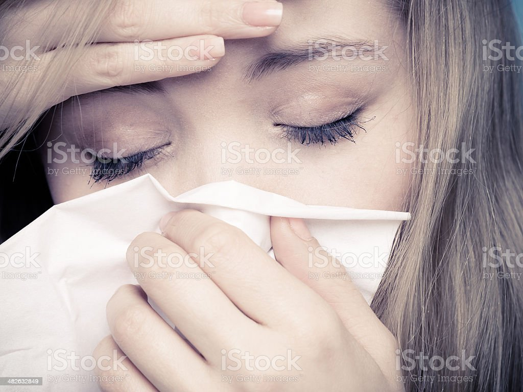 Flu fever. Sick girl sneezing in tissue. Health stock photo