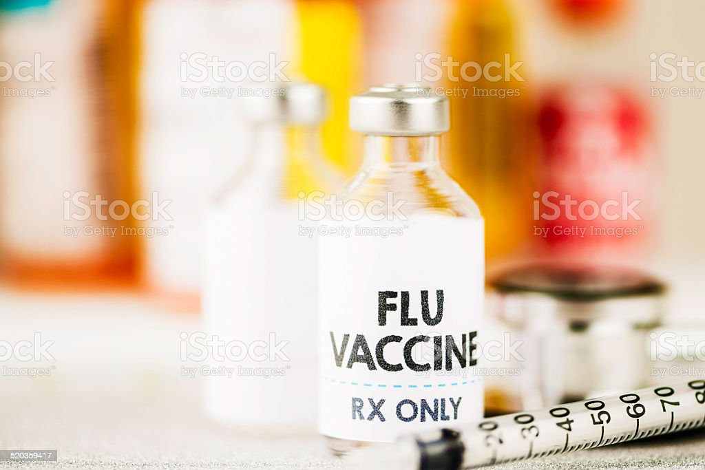 Flu vaccine with syringe and stethoscope stock photo