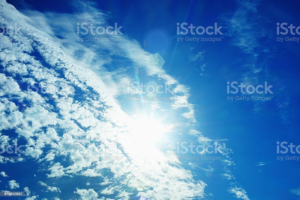 Fluffy clouds float across the midday sun stock photo