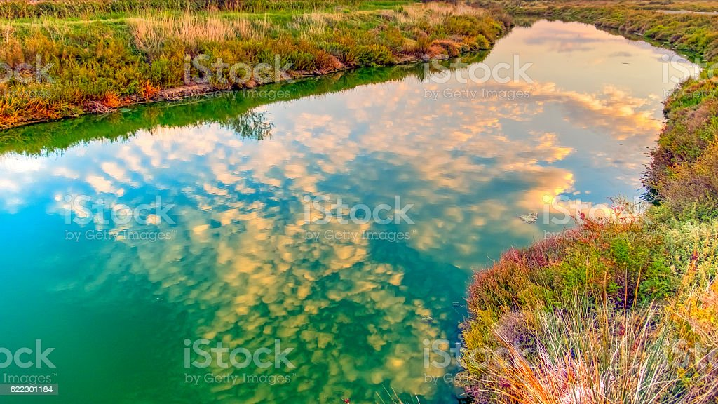Fluffy clouds reflect in colourful Camargue canal at sunset stock photo