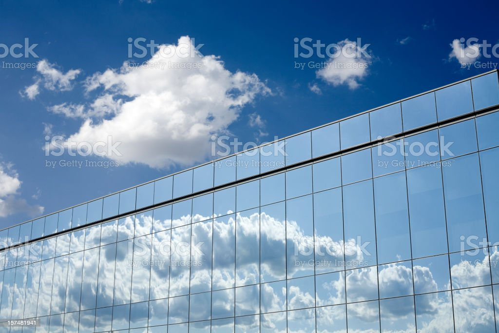 Fluffy clouds reflecting off a mirrored office building royalty-free stock photo