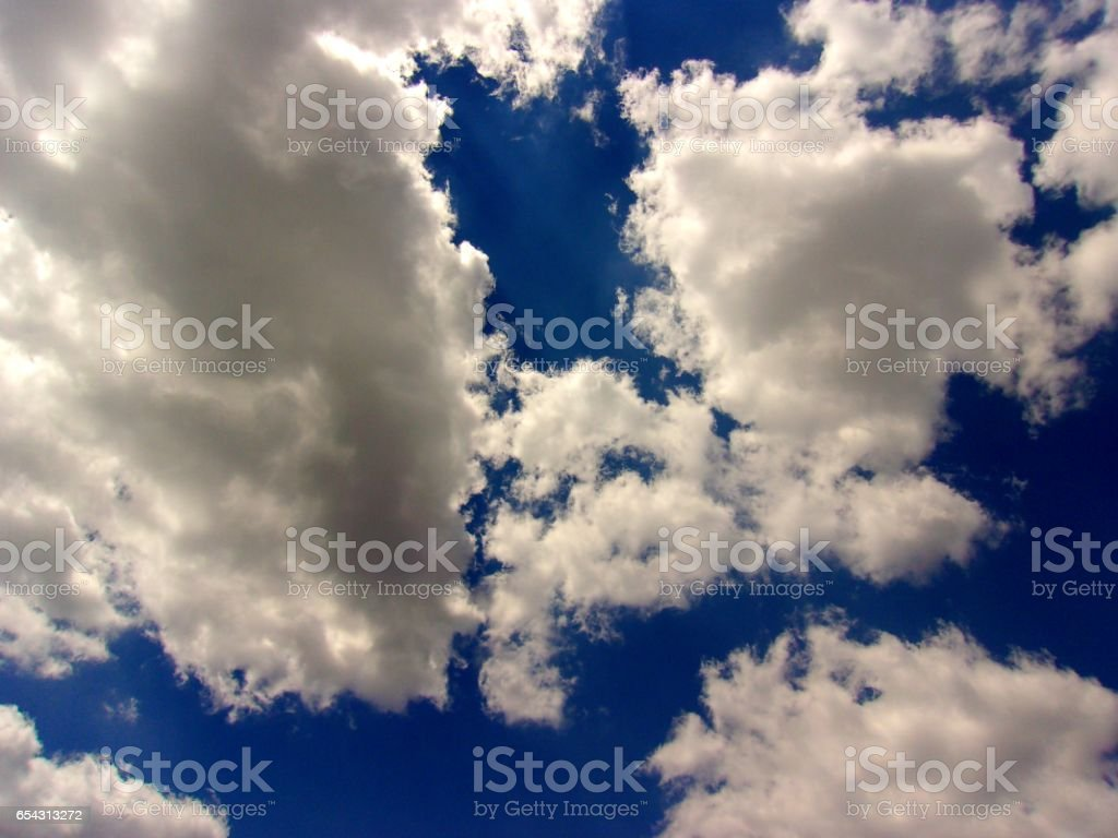 851- Fluffy clouds vibrant background stock photo
