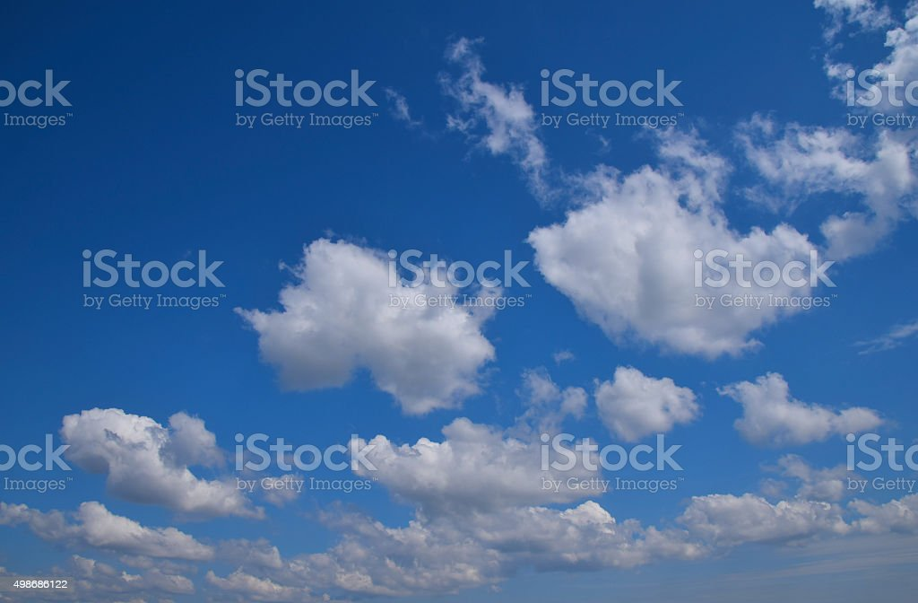 Fluffy ethereal white clouds in vivid blue sky royalty-free stock photo