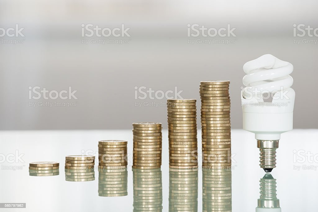 Fluorescent Light Bulb And Stacked Coins On Desk stock photo