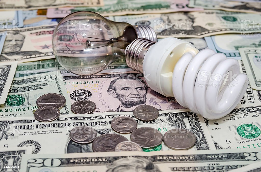 Fluorescent Light bulb on dollar background stock photo