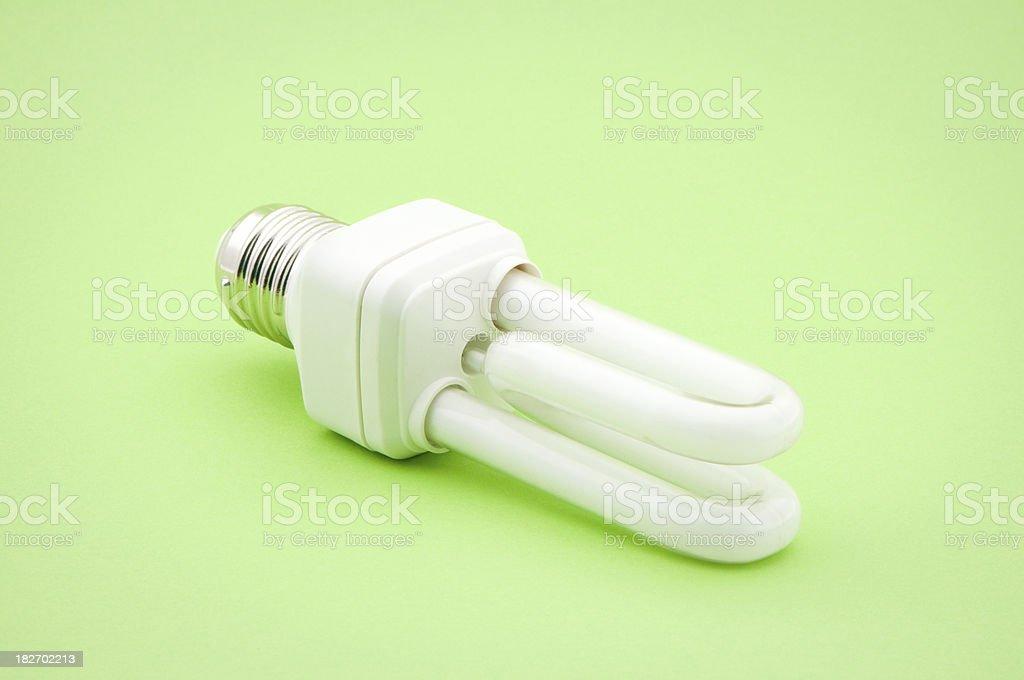 Fluorescent lightbulb isolated on green background stock photo