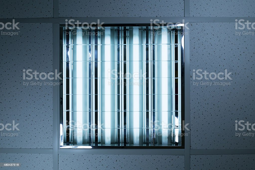 Fluorescent lights in office ceiling stock photo