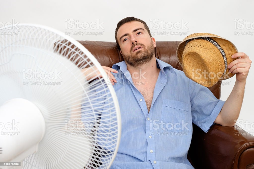 Flushed man feeling hot in front of a fan stock photo