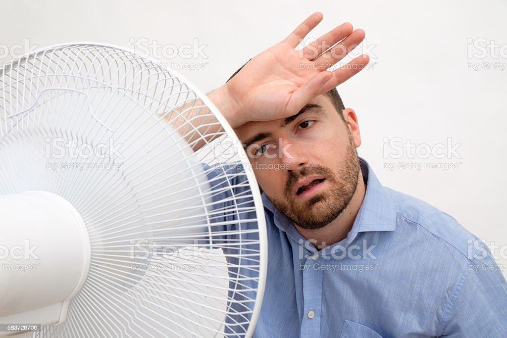 Flushed man feeling hot in front of a fan stock photo