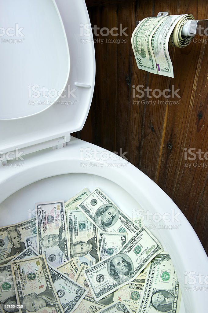 Flushing Money in the Toilet stock photo