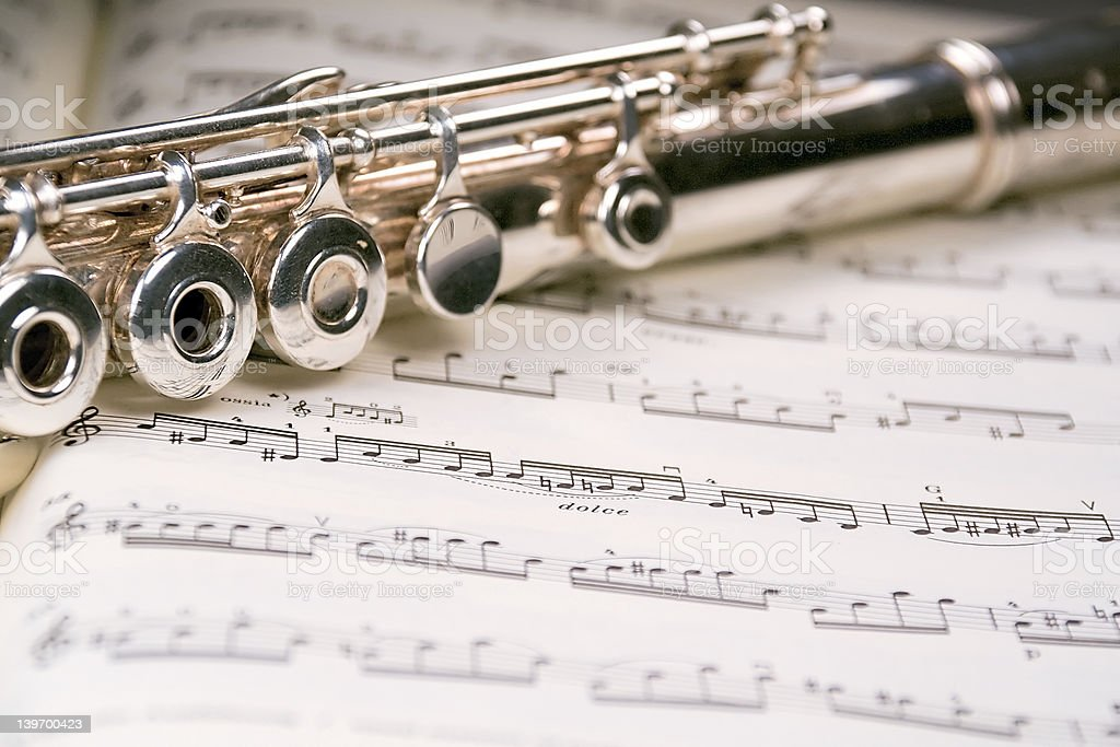 Flute across a musical score stock photo
