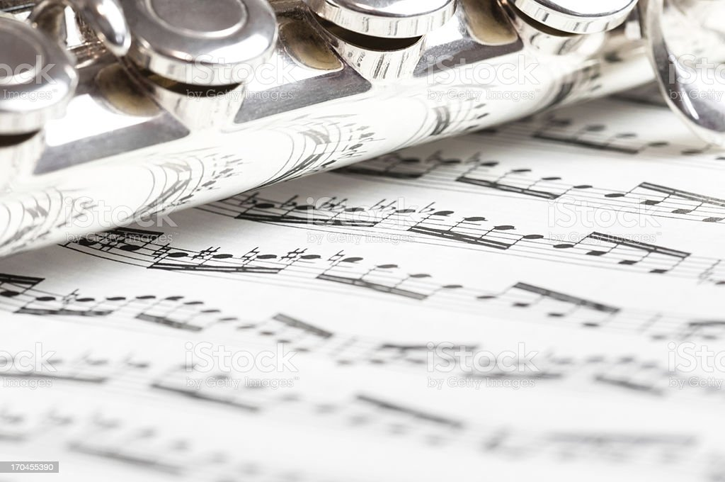 Flute keys on music notes stock photo