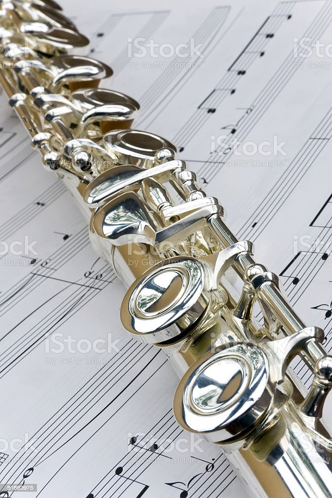 Flute lay across sheet music royalty-free stock photo