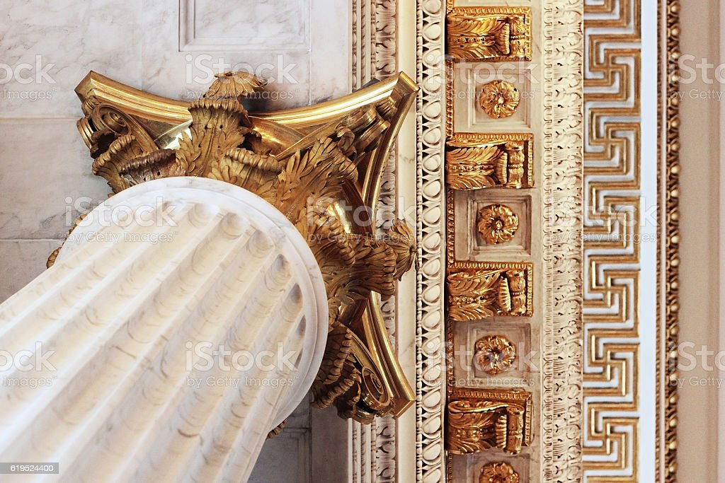 Fluted baroque column with gilded Corinthian capital supporting fretwork ceiling stock photo