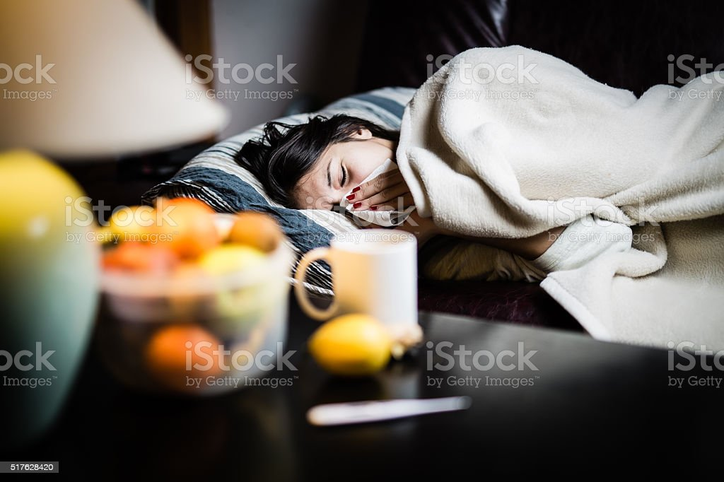 Flu.Woman Caught Cold.Virus.Sick woman laying in bed under wool blanket stock photo