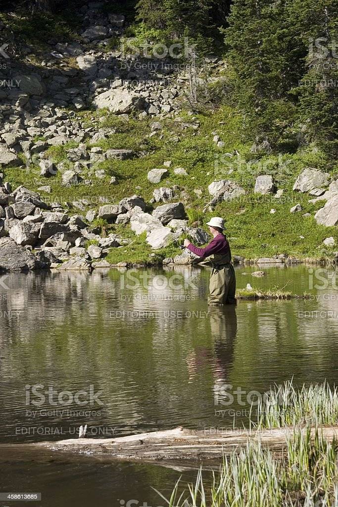 Fly fisherman casting for trout In a mountain lake stock photo