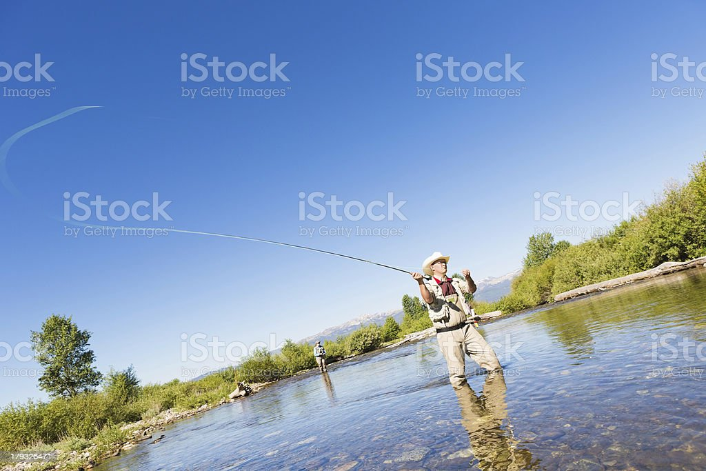 Fly fisherman casting line in river on sunny day stock photo