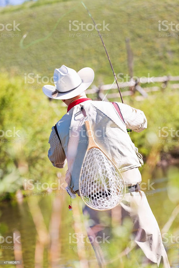 Fly fisherman casting line while fishing in Montana river royalty-free stock photo